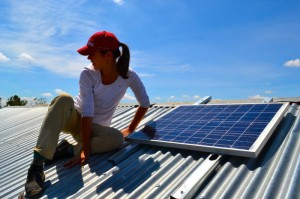 Franny installing solar panels on the roof for Napenda Solar Community