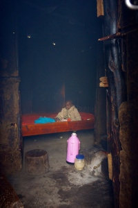 A young child sleeps in a smoke filled room due to the family using open fire for lighting.